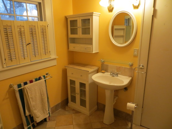 Pre reno yellow bathroom with pedestal sink and storage