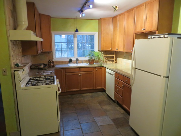 Green kitchen with wood cabinets and stone tile