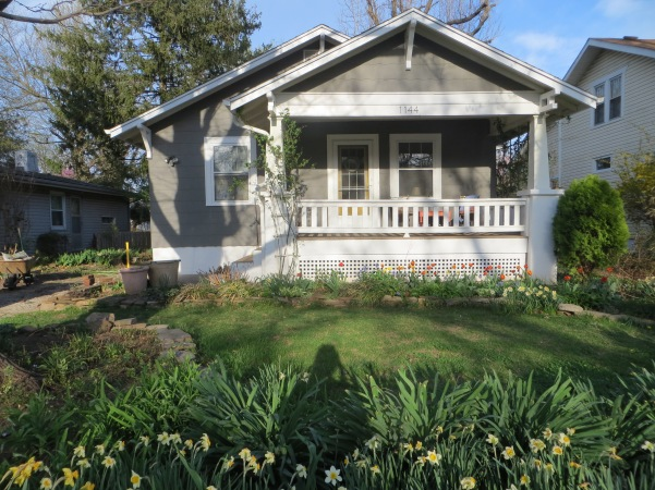 Dark gray bungalow with a yellow door and white trim