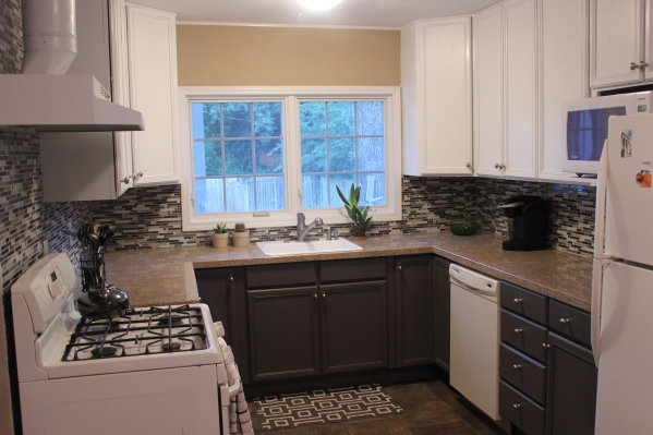 Two tone white and gray cabinets with glass mosaic tile