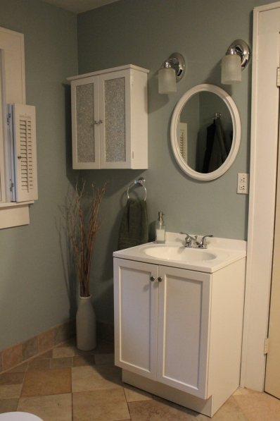 Light blue bathroom with white cabinets and ceramic tile