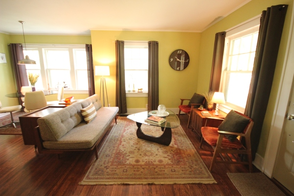 Green living room with platform couch, Noguchi style table, Buckstaff chairs