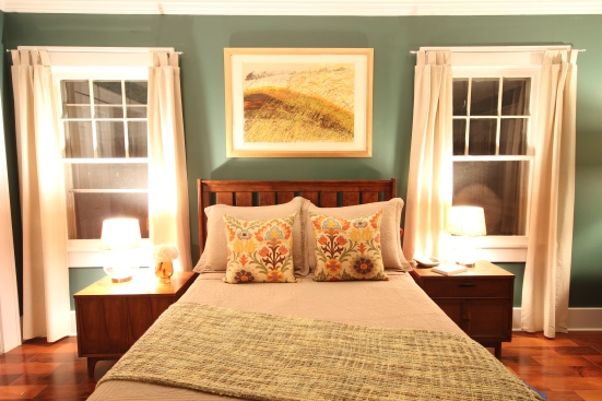 Dark green bedroom, neutral curtains, printed pillows, framed art above bed