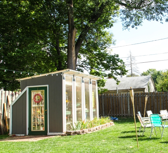 Cute garden shed greenhouse. Backyard with tiki torches. Green door with gray house.
