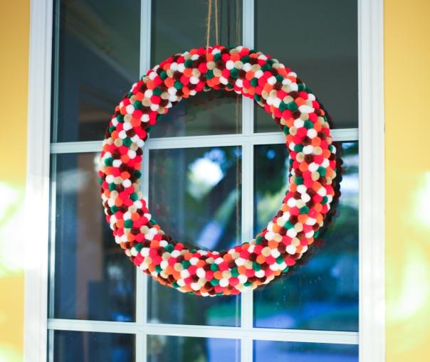 DIY colorful pom pom wreath on yellow door.