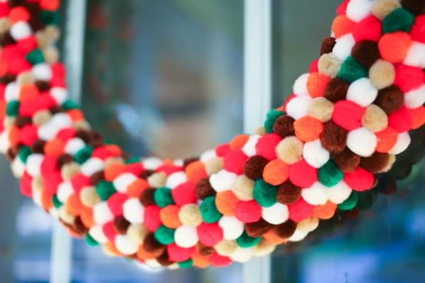 Multicolor brown, green, red, white, orange, green pom pom wreath.