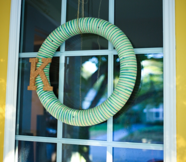 DIY striped yarn wreath with cork letter on my yellow door.