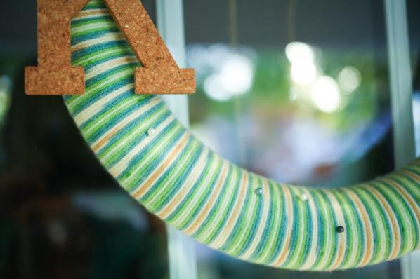Multicolor yarn made a striped yarn wreath. I added pearl head pins for embellishment.