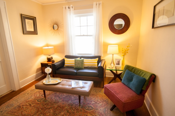 Cream walls, mid-century furniture, symmetrical mirrors.